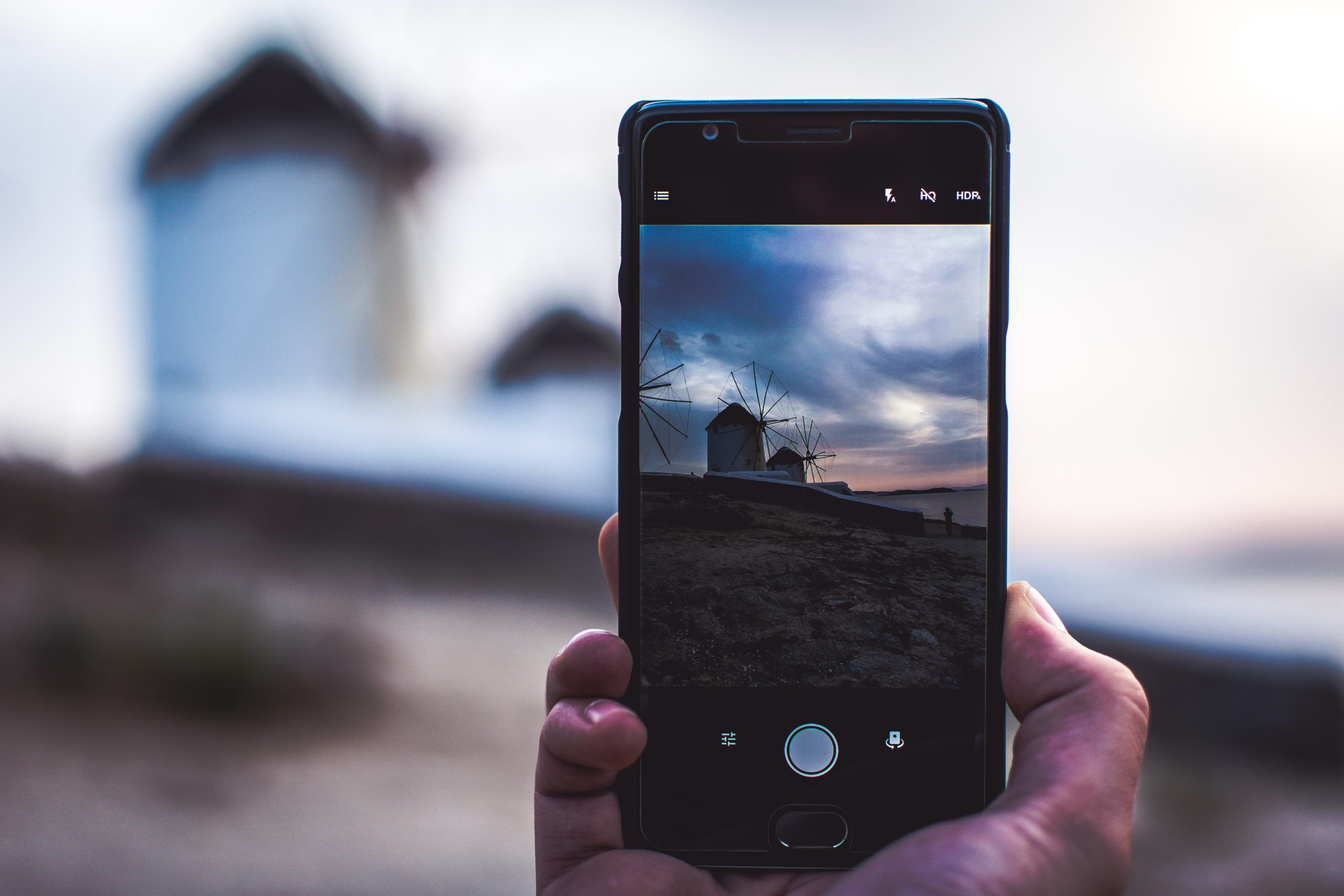 man using phone taking photo of the house